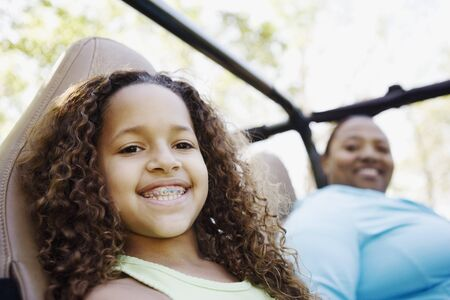 relishing: African mother and daughter sitting in jeep smiling LANG_EVOIMAGES