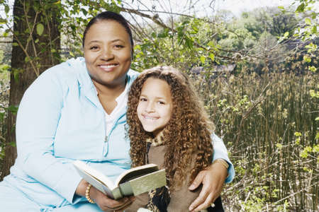 adoring: African mother and daughter reading outdoors LANG_EVOIMAGES