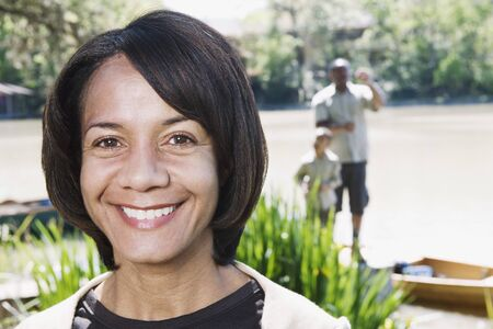 middleaged: Middle-aged African woman smiling with family in background