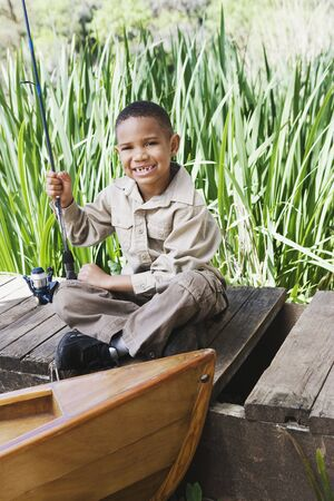 fishing pole: Young African boy on dock with fishing pole