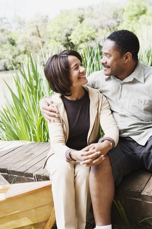 Middle-aged African couple smiling on dock Stock Photo