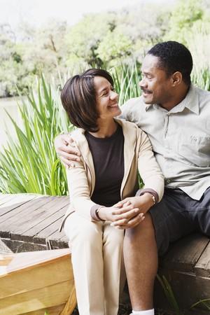midsummer pole: Middle-aged African couple smiling on dock LANG_EVOIMAGES