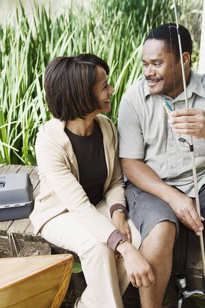 courting: Middle-aged African couple smiling with fishing gear