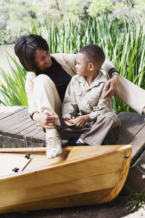 casualness: African mother and son sitting on dock next to canoe