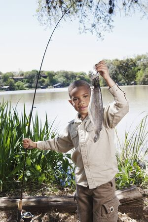 fishing pole: Young African boy with fishing pole and fish