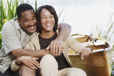 midsummer pole: Middle-aged African couple laughing next to canoe