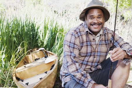 Middle aged African man with fishing gear next to canoe Imagens