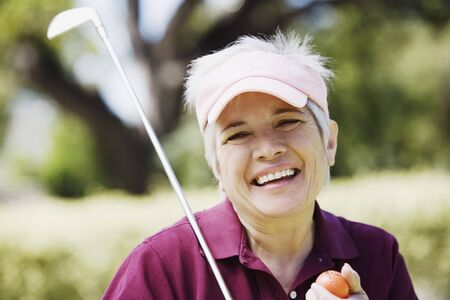 middleaged: Middle-aged woman with golf club and golf ball