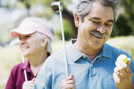 Middle-aged couple with golf clubs