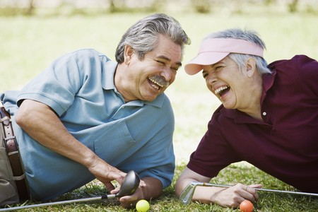 Middle-aged couple laughing with golf clubs