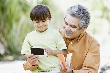 Father and son looking at photographs outdoors
