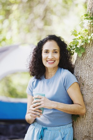 adventuresome: Woman leaning on tree next to tent