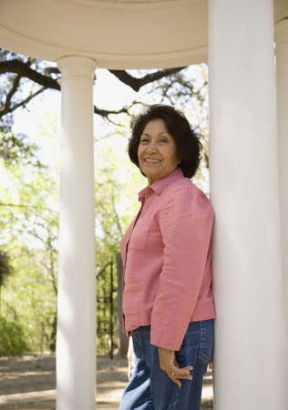 mid life: Senior woman leaning on column outdoors LANG_EVOIMAGES