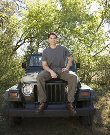 leaning on the truck: Young man sitting on jeep in woods LANG_EVOIMAGES