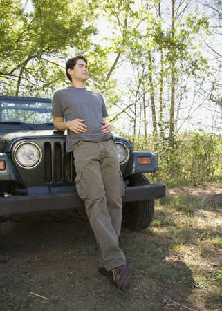 leaning on the truck: Young man leaning on jeep in woods LANG_EVOIMAGES