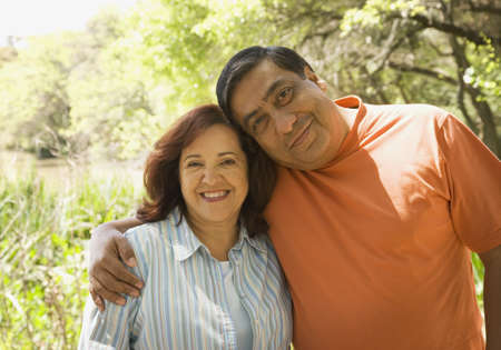 Middle-aged Hispanic couple hugging outdoors Stock Photo