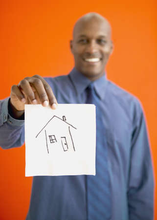 bestowing: African man holding up napkin with house drawn on it