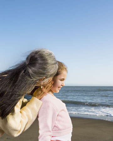 stepping: Grandmother whispering in a granddaughterís ear LANG_EVOIMAGES