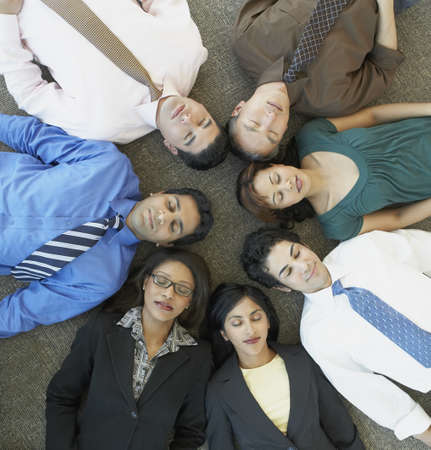 appendage: High angle view of businesspeople laying on floor with eyes closed
