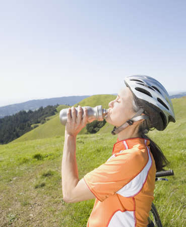 bicycling: Woman in bicycling gear drinking from water bottle LANG_EVOIMAGES