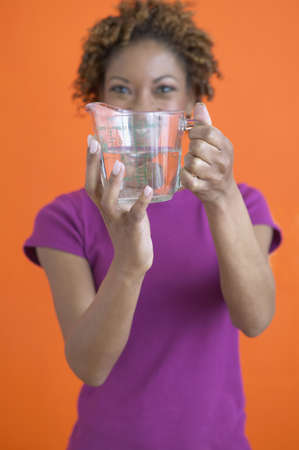gramma: African woman holding measuring cup with water LANG_EVOIMAGES