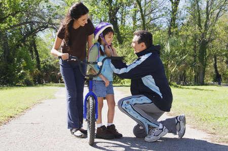 irish ethnicity: Hispanic father helping daughter fasten bicycle helmet