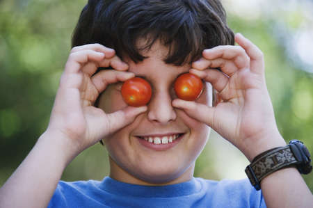 poppa: Boy holding cherry tomatoes up to his eyes