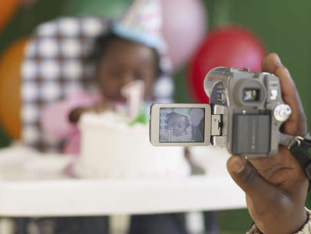 fathering: African father videotaping baby in high chair with birthday cake