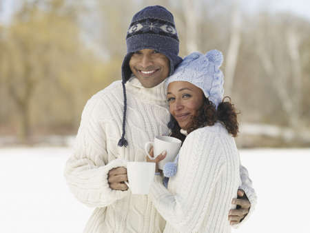 poppa: African couple hugging in hats and sweaters LANG_EVOIMAGES