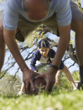 native american baby: Man hiking football to girl