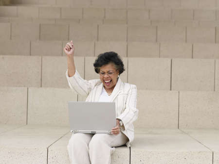 Senior African businesswoman using laptop on steps outdoors LANG_EVOIMAGES