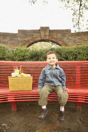 german ethnicity: Young boy with picnic basket on bench