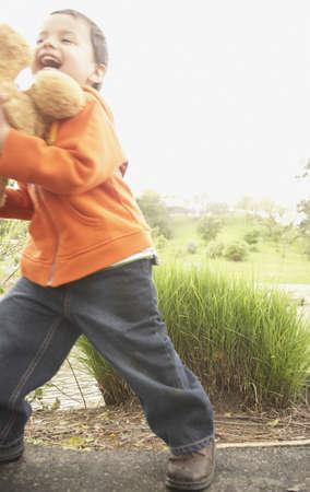 three generation: Young boy running with teddy bear