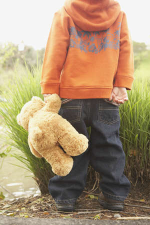 wanting: Rear view of young boy with teddy bear