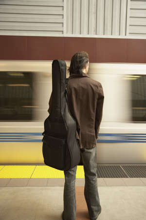 Rear view of man with guitar waiting for train Stock Photo