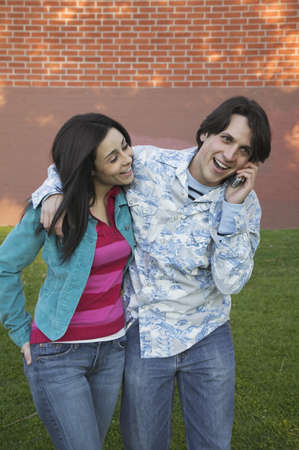 longshot: Young Hispanic couple using cell phone outdoors LANG_EVOIMAGES
