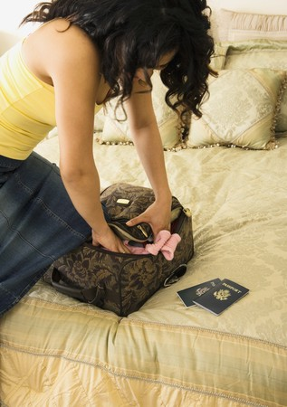 mischeif: Woman packing suitcase on bed