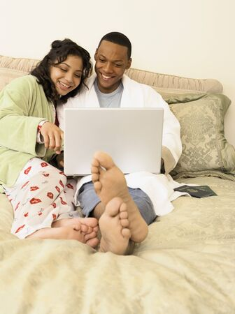 African couple in pajamas using laptop in bed