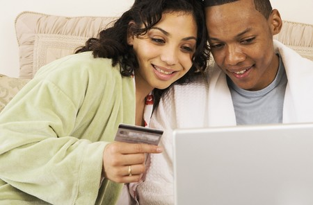 searcher: African couple with credit card using laptop in bed