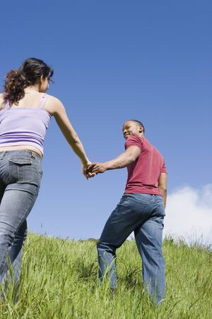 Couple holding hands and walking up hill