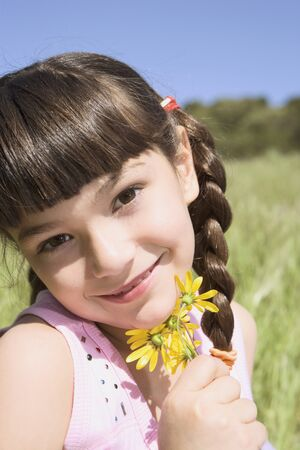 devilment: Young Hispanic girl holding flowers outdoors