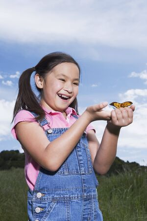 Young Asian girl holding butterfly outdoors Stock Photo