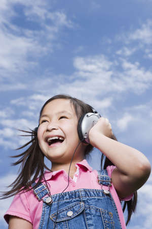 Young Asian girl holding listening to music outdoors