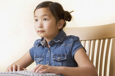 Young Asian girl using computer LANG_EVOIMAGES