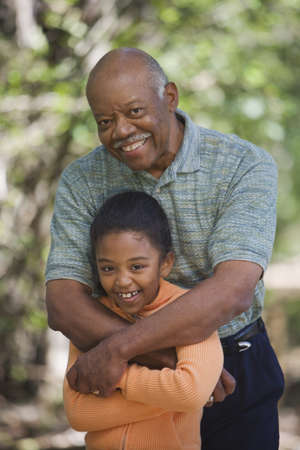 African grandfather and young granddaughter hugging