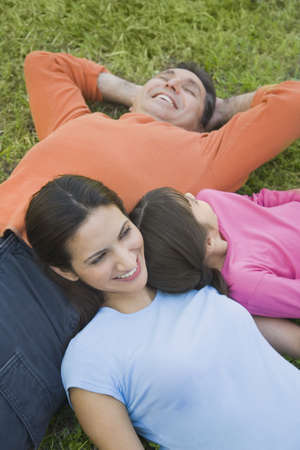 fathering: Hispanic family laying in grass