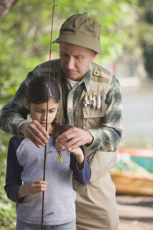 midsummer pole: Hispanic grandfather helping granddaughter with fishing pole LANG_EVOIMAGES