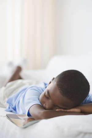 ojos negros: Muchacho africano joven que duerme con el libro en el sof� LANG_EVOIMAGES