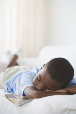 happy black man: Young African boy sleeping with book on sofa LANG_EVOIMAGES