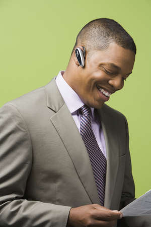 earpiece: African businessman with earpiece smiling